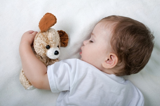 Little child sleeping with teddy bear